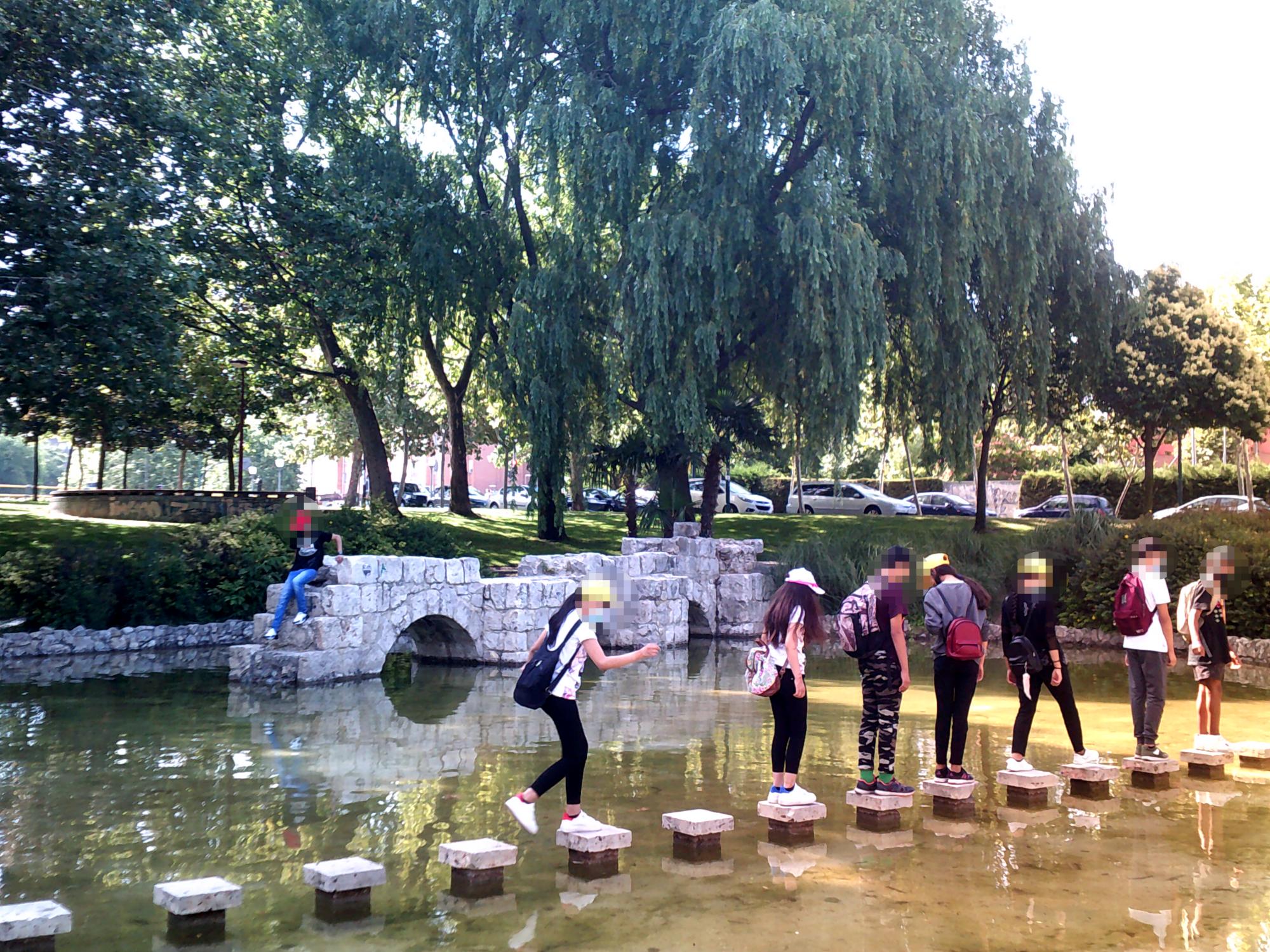 Grupo de personas encima de varias piedras en un estanque artificial, y al fondo los arcos de piedra que marcaban una de las entradas de mercancías a Valladolid