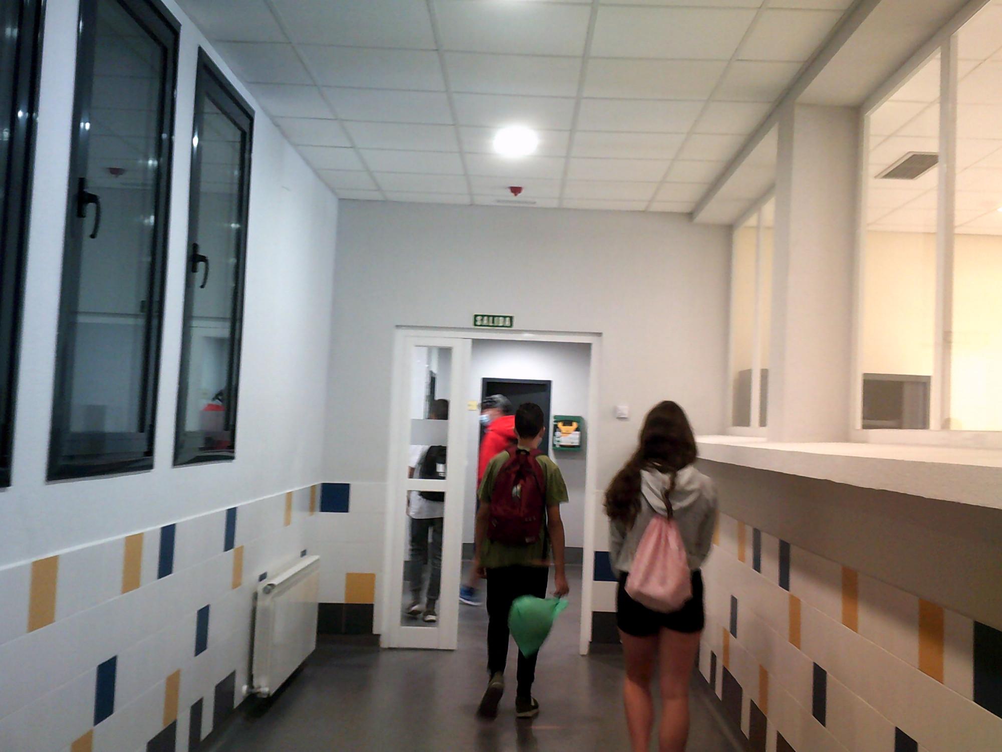 Pasillo interno del CIC Segundo Montes, y gente saliendo, se ven las espaldas