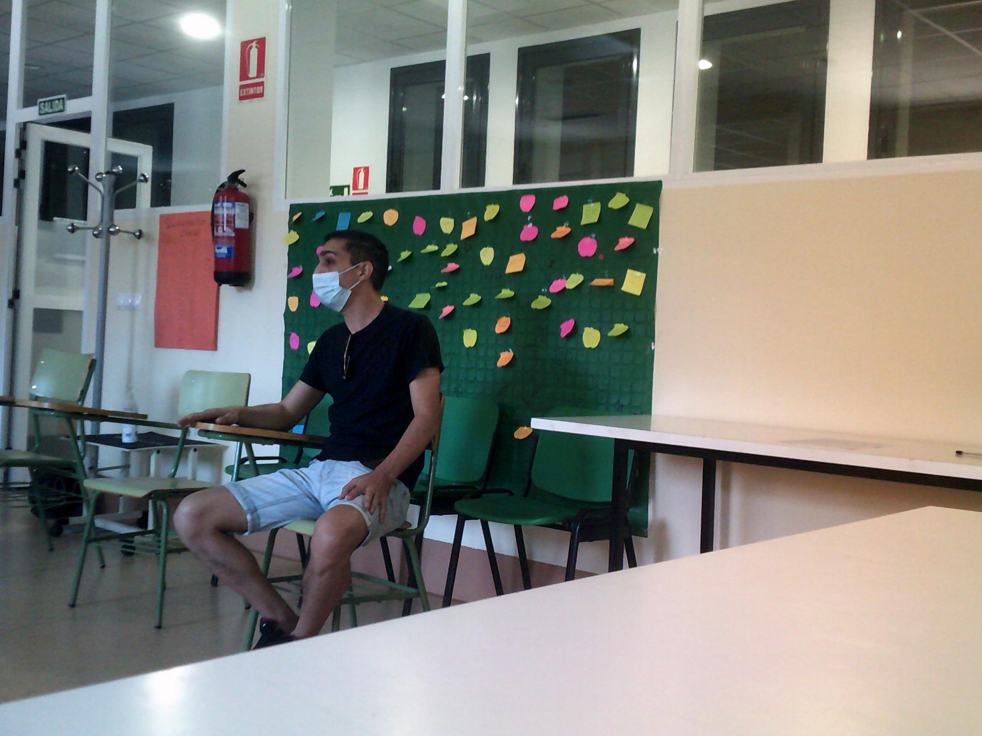 David sentado en una silla del aula mientras habla